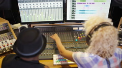 4K Man & woman in recording studio working at the mixing desk Stock Footage