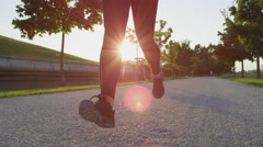 SLOW MOTION CLOSE UP: Female in black leggings jogging in tree avenue in evening Stock Footage