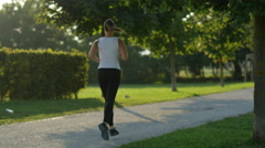 SLOW MOTION: Young sporty woman running in amazing tree promenade in green park Stock Footage