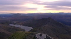 Drifting left to right behind the summit of Snowdon at dawn. Stock Footage
