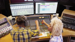 4K Sound engineer & female artist working at the mixing desk in recording studio Stock Footage