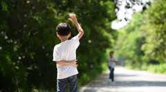 Two boy walk and run and wave their hand to meet each other on the urban road an Stock Footage