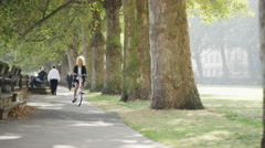 4K Cheerful professional woman riding bicycle in city park Stock Footage