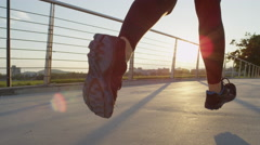 SLOW MOTION: Female runner running across city bridge into magical rising sun Stock Footage