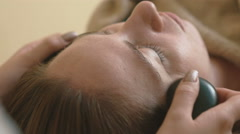 Young woman doing hot stone massage spa Stock Footage