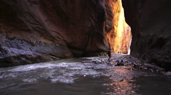 Woman hiking through a slot canyon in Zion National Park  Stock Footage