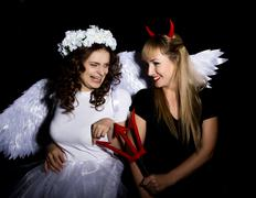 Portrait of angel and devil womans on a dark background Stock Photos