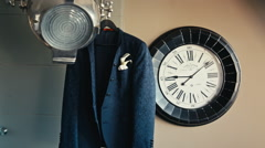Men's jacket hanging on the floodlight near the clock Stock Footage