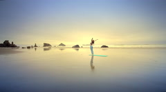 Young woman doing Yoga on Pacific Ocean beach at sunset. Stock Footage