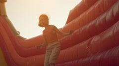 Little girl jumping on an inflatable trampoline Stock Footage