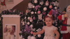 Repeating of a small girl posing nearby the Christmas tree in a Santa's cap Stock Footage