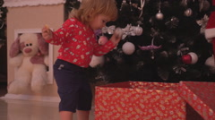 Little mother's helper decorating the Christmas tree and eating Ginger Bread Stock Footage