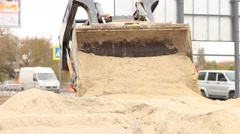 Yellow excavator with sand working on a road Stock Footage