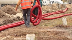 Workers laying cable while road working Stock Footage