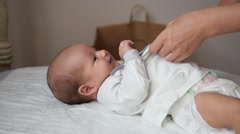 Female hands clothing a cute baby in nappy. Handheld shot Stock Footage