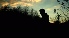 Man manages drone. Silhouette against the sunset sky Stock Footage