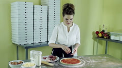 A young woman putting pieces of salami on a pizza greased with tomato sauce. HD Stock Footage
