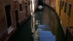 Tilt up from reflection in water to old buildings in an alley in Venice Stock Footage