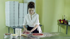 A young woman putting pieces of bacon on a pizza greased with tomato sauce. HD Stock Footage