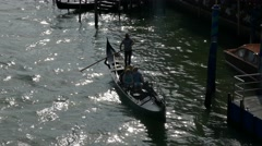 Silhouette Gondolier steering boat standing on gondola transporting tourists Stock Footage