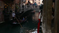 Gondolier steering gondola take tourists in tiny small canal going under bridge Stock Footage