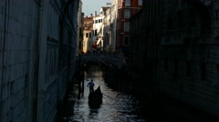 Silhouette Gondolier steering boat on gondola with tourists in tiny small canal Stock Footage