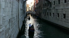 Gondoliers steering boat on gondola with tourists in tiny small canal Stock Footage