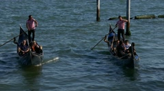 Gondoliers steering boat standing on gondola transporting tourists grand canal Stock Footage