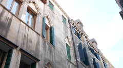 Tilt down old buildings in an alley in Venice, drying clothes outside the window Stock Footage