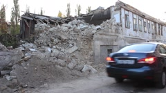 Cars passing a street near the destroyed building Stock Footage
