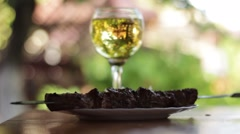 Glass of white wine and fried meet on a table outdoors Stock Footage