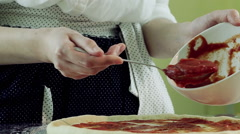 Cooking pizza. Female hands adding and spreading tomato sauce on tasty pizza. HD Stock Footage