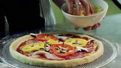 Female hands pouring cheese on pizza base with bacon, salami and bell pepper. HD Stock Footage