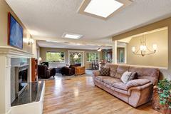 Open plan family room with hardwood floor, fireplace, skylights on the ceilin Stock Photos
