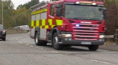 Fire engine with sirens wailing speeds around corner in Lichfield England Stock Footage