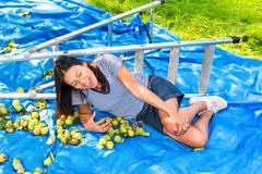 Fallen young woman lying injured on ground near ladder Stock Photos