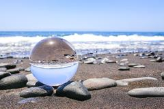 Glass sphere on stones at beach in Madeira Stock Photos