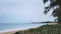 Profile of a commercial plane flying over the sea about to land Stock Footage