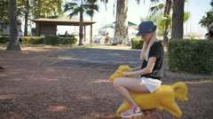 Young beautiful woman ride toy horse in a park playground Stock Footage