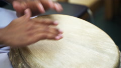 Closeup of man's hands drumming out a beat on an skin-covered bongo hand drum  Stock Footage
