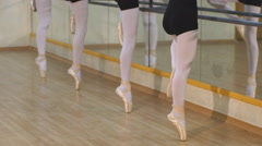 Young ballet dancers stands near the ballet barre at the ballet hall Stock Footage