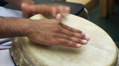 Closeup man's hands drumming out beat on skin-covered bongo hand drum. SLOW MO  Stock Footage