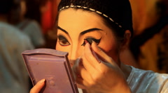 A Chinese opera performer applies make-up Stock Footage
