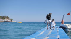 Mother and girl walks on pier, swing by waves Stock Footage
