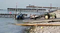 Tractor pulls a boat out of the water .  beach on the Kinneret. Stock Footage