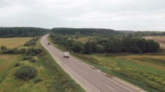 Aerial view of car driving on a road in the woods Stock Footage