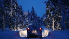 Night Snowfall in the Winter Forest and a Car with Headlights Stock Footage