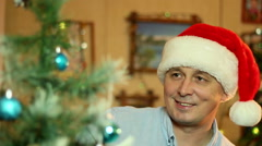 A young man  decorates a Christmas tree in the house Stock Footage