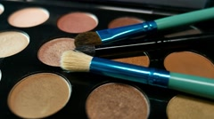 Footage of a make up palette and some brushes lying on it, the shot is moving Stock Footage