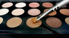 A front shot of a make-up artist takes a brush and uses two different colors Stock Footage